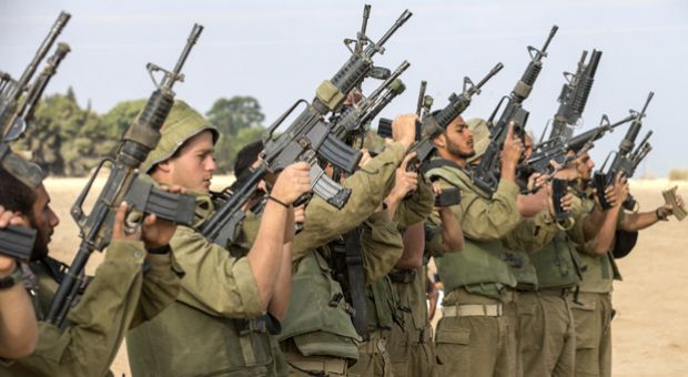 Israeli soldiers check their weapons at an army deployment area, on the southern Israeli border with the Gaza Strip, on August 1, 2014, after the proposed three-day truce collapsed amid a deadly new wave of bloodshed and the apparent capture of an Israeli soldier by Hamas.
