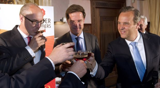 Michiel Herkemij (L), CEO of D.E Master Blenders 1753, a global coffee and tea business, accompanied by Dutch Prime Minister Mark Rutte (C) and CEO of Euronext Cees Vermaas, celebrate after sounding the bell during the opening of trading on the European markets of NYSE Euronext in Amsterdam, on June 12, 2012. The company split from U.S.-based Sara Lee Corp so it could begin trading in Amsterdam.
