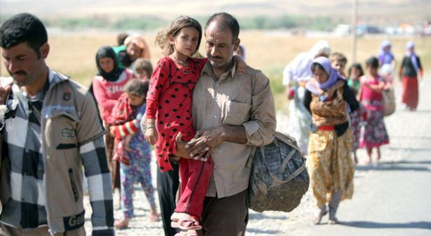 A displaced Iraqi man from the Yazidi community carries his daughter as they cross the Iraqi-Syrian border at the Fishkhabur crossing in northern Iraq, on August 11, 2014. At least 20,000 civilians, most of whom are from the Yazidi community, who had been besieged by jihadists on a mountain in northern Iraq have safely escaped to Syria and been escorted by Kurdish forces back into Iraq, officials said.