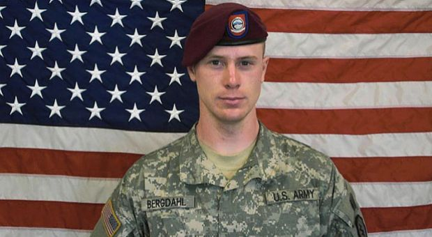 In this undated image provided by the U.S. Army, Sgt. Bowe Bergdahl poses in front of an American flag.