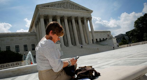 Kirsten Luna from Holland, Michigan, uses her smartphone outside the U.S. Supreme Court after a major ruling on cell phone privacy by the court June 25, 2014 in Washington, D.C. The Supreme Court issued a ruling requiring law enforcement officials to have a search warrant to search the cellphones of suspects they arrest.