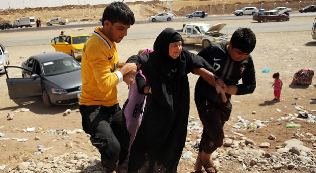An elderly Iraqi woman is helped into a temporary displacement camp for Iraqis on June 26, 2014 in Khazair, Iraq. Tens of thousands of people have fled Iraq's second largest city of Mosul after it was overrun by ISIS (Islamic State of Iraq and Syria) militants.