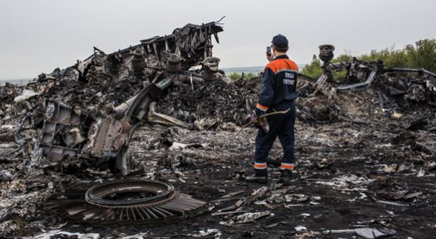 An emergency services worker photographs debris from an Malaysia Airlines plane crash on July 18, 2014 in Grabovka, Ukraine.
