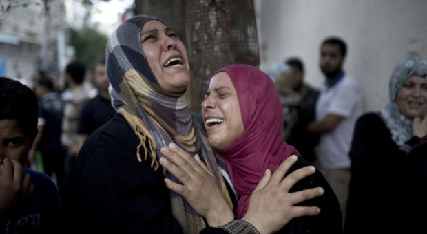 Palestinian women grieve over the death of relatives outside the morgue of the Kamal Adwan hospital in Beit Lahiya, on July 24, 2014, after a UN school in the northern Beit Hanun district of the Gaza Strip was hit by an Israeli shell.