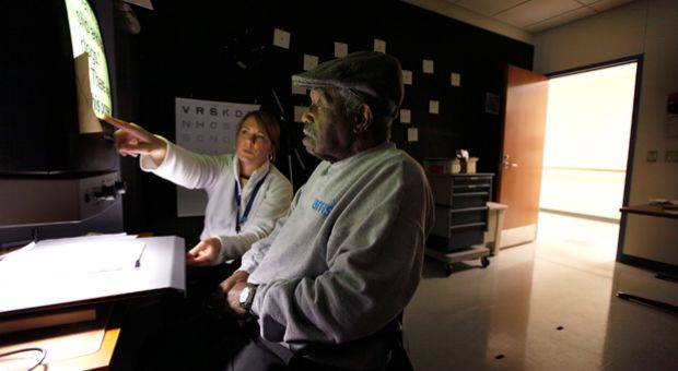 Kristin Reinhart helps Elwood Crowder learn to use a reading aid at the Central Blind Rehabilitation Center at the Edward Hines Jr. VA Hospital  in Hines, Illinois.