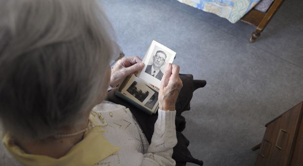 A woman, suffering from Alzheimer's disease, looks at an old picture on March 18, 2011 in a retirement house.