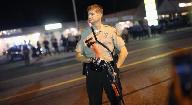 Police watch as demonstrators protest the shooting death of Michael Brown along West Florissant Avenue on August 23, 2014 in Ferguson, Missouri.