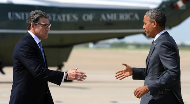US President Barack Obama (R) is greeted by Texas Governor Rick Perry in Dallas, Texas, on July 9, 2014 as he arrives for a meeting with local elected officials and faith leaders to discuss the urgent humanitarian situation at the Southwest border.