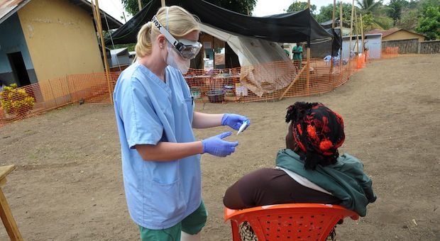 A nurse of the 'Doctors without Borders' medical aid organization examines a patient in the in-take area at a center for victims of the Ebola virus in southern Guinea.