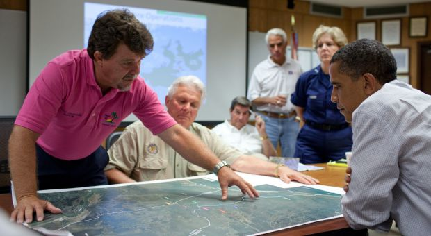 Grand Isle (Louisiana) Mayor David Camardelle points out areas on a map relating to the BP oil spill during a briefing with President Barack Obama at the U.S. Coast Guard Station in Grand Isle, La., May 28, 2010.