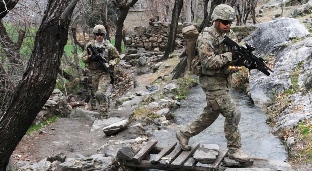 Spc. Jesus B. Fernandez crosses a stream during a unit visit to Angla Kala village in Afghanistan's Kunar province, Feb. 6, 2010. International Security Assistance Force troops regularly meet with village elders to improve communications between residents and government officials.