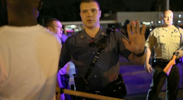 Police officers tell people to back up in Ferguson, Missouri.