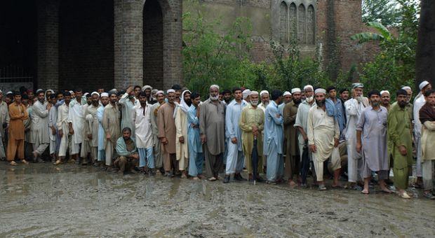 People waiting in line for aid at a tent distribution point in northwest Pakistan