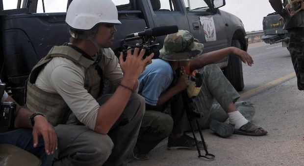 A photo taken on September 29, 2011 shows US freelance reporter James Foley (L) on the highway between the airport and the West Gate of Sirte, Libya. A video released this week shows an ISIS militant beheading Foley in what is believed to be retaliation for U.S. airstrikes in Iraq