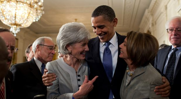 President Barack Obama embraces Secretary of Health and Human Services Kathleen Sebelius, left, and House Speaker Nancy Pelosi after signing the health insurance reform bill in the East Room of the White House, March 23, 2010