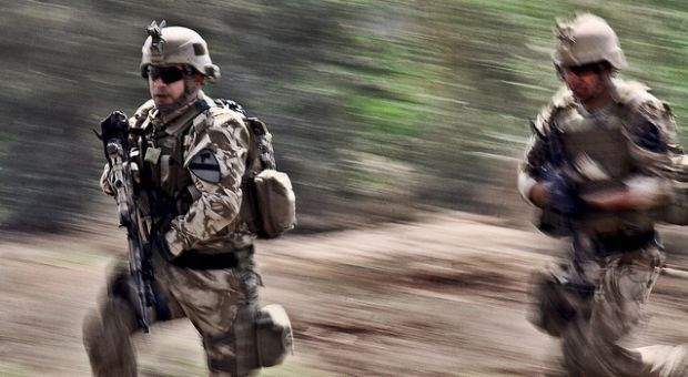 Karkh Area Command Strike Team soldiers rush onto a simulated battlefield during a joint air assault demonstration on Camp Taji, Iraq, March 29, 2010