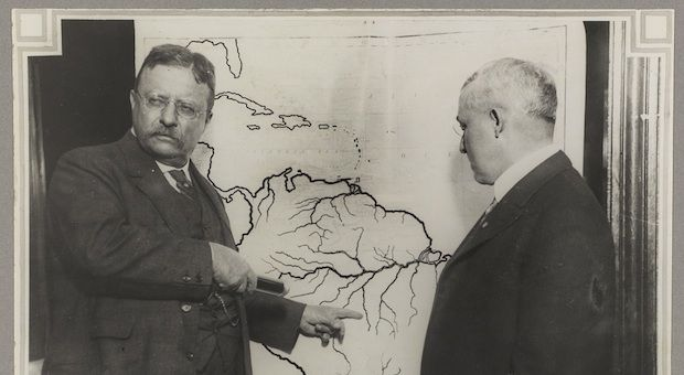 President Roosevelt points at a map of South America to highlight the area explored during the Roosevelt-Rondon Scientific Expedition in Brazil.