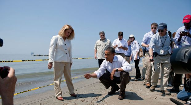 President Barack Obama and Lafourche Parish President Charlotte Randolf, left, inspect a tar ball as they look at the effect the BP oil spill is having on Fourchon Beach in Port Fourchon, La., May 28, 2010